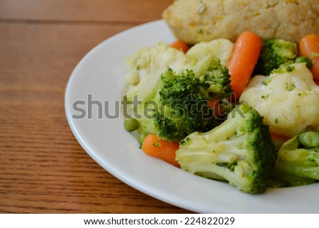 Healthy meal with broccoli, carrot, cauliflower and steamed fishcake - stock photo