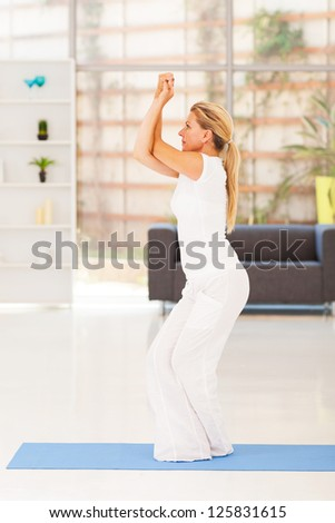 healthy middle aged woman doing yoga at home - stock photo