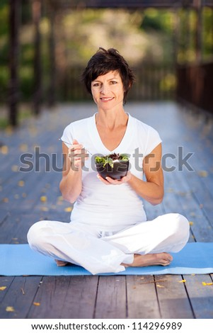 healthy middle aged woman eating salad outdoors - stock photo