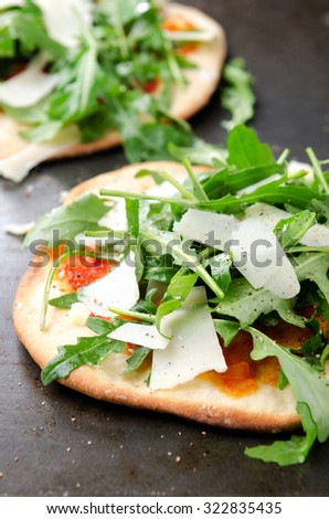 Healthy mini pizzas with fresh rocket and shaved parmesan cheese - stock photo