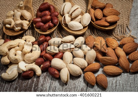 Healthy mix nuts on wooden background. Almonds, hazelnuts, cashews, peanuts, brazilian nuts - stock photo
