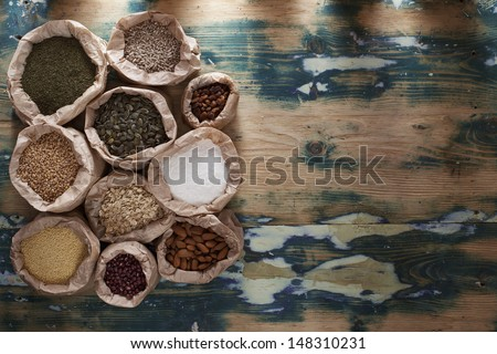 Healthy mix. Various types of beans, seeds, nuts and grains in paper bags on a rustic wooden table. Grain texture added. - stock photo
