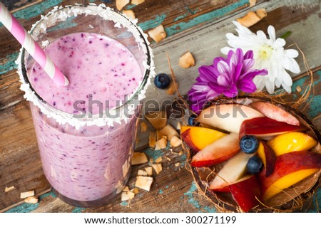 Healthy mixed berry smoothie milkshake made from blended blueberries, strawberries  with yogurt. Served in a coconut frosted glass with a stripey straw. With sliced peaches in a coconut shell.  - stock photo