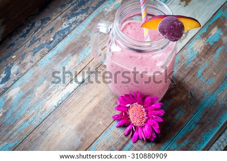 Healthy mixed berry smoothie milkshake made from blended blueberries, strawberries  with yogurt. Served in a jug style glass and garnished with fruit and a fresh wild flower. - stock photo