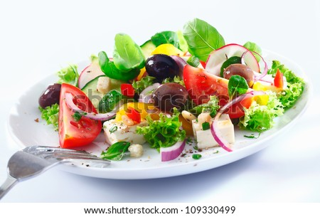 Healthy mixed Greek salad served on a white plate with silver fork containing crisp leafy greens, olives, feta, onion , tomato, cucumber and radish - stock photo