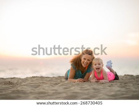 Healthy mother and baby girl laying on beach in the evening - stock photo