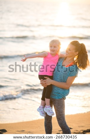 Healthy mother and baby girl pointing while on beach in the evening