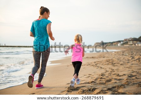 Healthy mother and baby girl running on beach. rear view - stock photo