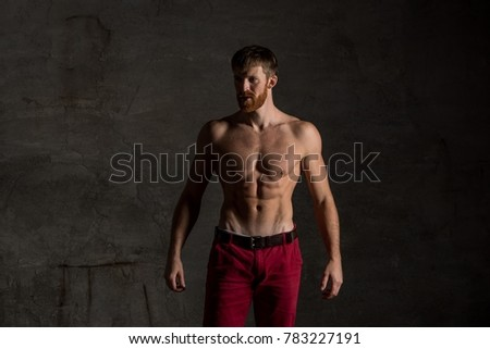Healthy muscular bearded man on dark background