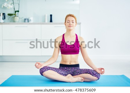 Healthy muscular red haired woman practicing yoga at home in bright sportswear, sitting on mat in lotus position with eyes closed, breathing calmly, relaxing and meditating