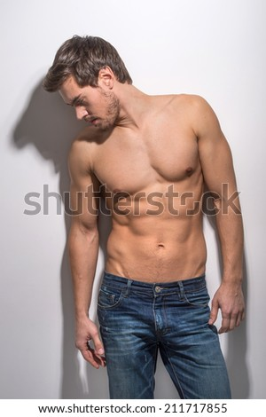 Healthy muscular young man in jeans. Isolated on white background guy looking away.