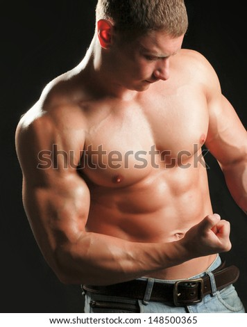 Healthy muscular young man. Isolated on black background - stock photo