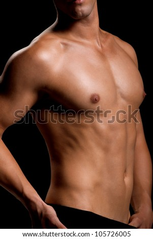 Healthy muscular young man. Isolated on black background.  Shallow DoF with focus on chest and neck. - stock photo
