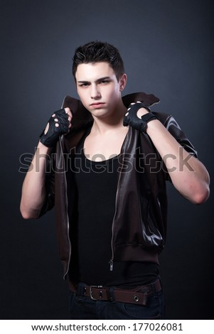 Healthy muscular young man on a black background. - stock photo