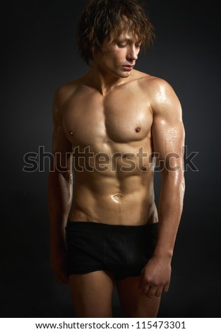 Healthy muscular young man on black background.
