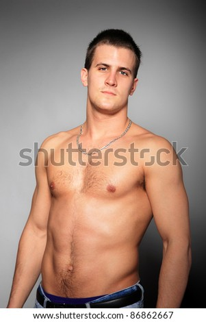 Healthy muscular young man. on gray background - stock photo