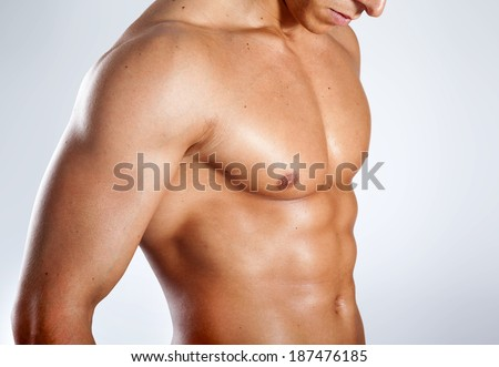 Healthy muscular young man on grey background - stock photo