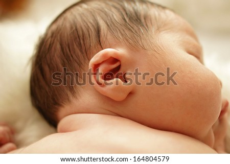 Healthy newborn baby sleeping, showing close up of ear and side of babies head - stock photo