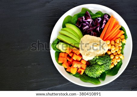 Healthy nourishment bowl with super-foods and fresh mixed vegetables, overhead view on dark slate