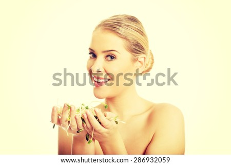 Healthy nude woman holding a cuckooflower.