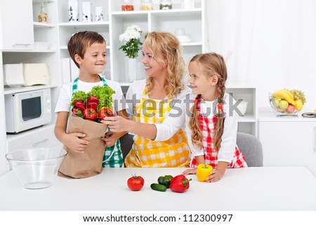 Healthy nutrition concept with people in the kitchen unpacking the vegetables from grocery bag