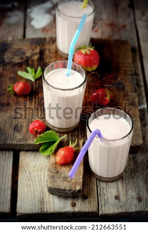 Healthy nutritious tropical smoothie with strawberries blended with yoghurt or ice cream on a rustic wooden table top - stock photo