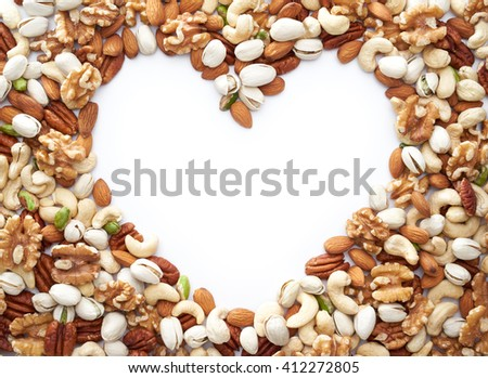 Healthy nuts framing a heart shape over white background  - stock photo