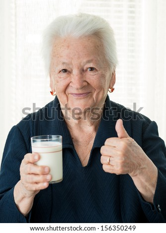 Healthy old woman holding a glass milk  - stock photo