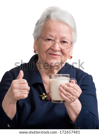 Healthy old woman holding a glass milk on a white background - stock photo