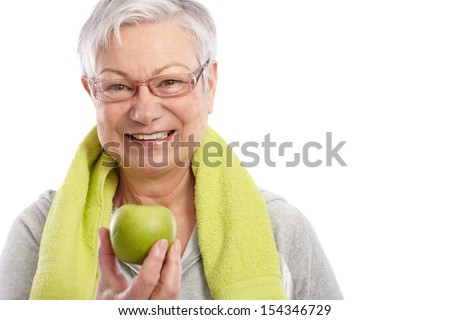 Healthy old woman holding green apple, smiling, towel around neck. - stock photo