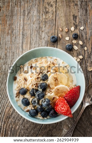 Healthy or dietetic breakfast - yoghurt with oat flakes, blueberries, banana and strawberries in pastel blue bowl on an old vintage wood table. View from above, layout with free text space. - stock photo