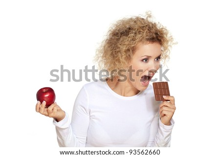 Healthy or unhealthy food? / Beautiful blond woman chooses to eat chocolate instead of red apple