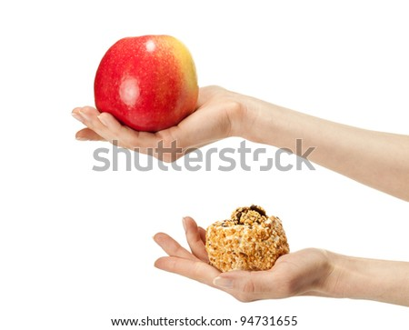 Healthy or unhealthy food? Hand holding apple and cake demonstrating process of choosing