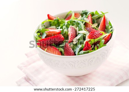 Healthy organic diet salad with arugula, strawberries, swiss chard and almonds in white bowl on pink napkin - stock photo