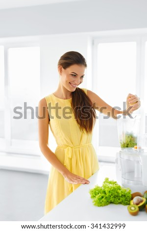 Healthy Organic Food Preparation. Green Juice. Happy Smiling Woman Juicing Vegetables And Fruits, Preparing Smoothie. Detox Diet. Healthy Eating, Vegetarian Raw Food Concept. - stock photo