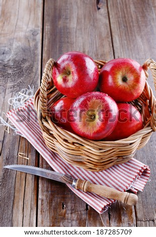 Healthy organic red apples in a straw basket and knife on a wooden background - stock photo
