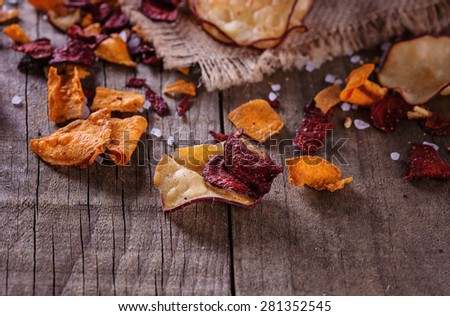 Healthy organic vegetable beetroot, sweet potato and white sweet potato chips over rustic background. Copy space; selective focus. Only central part of the image is in focus - stock photo