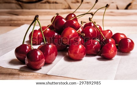 Healthy organic vegetarian super food cherries in clay dish on rustic kitchen table background. Dark photo, rustic style, natural light - stock photo