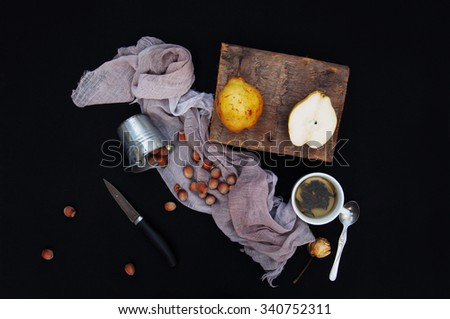 Healthy organic yellow pears on the desk. Fruit background. Ripe fresh organic  pears on black  background. Pear autumn harvest. Sliced pear on a chopping board. Top view.  Autumn harvest. Knife. Tea. - stock photo