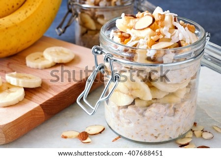 Healthy overnight oats with bananas and nuts in glass canning jars - stock photo
