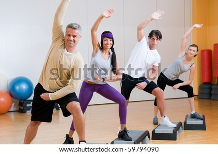 Healthy people doing aerobic exercises together at gym - stock photo