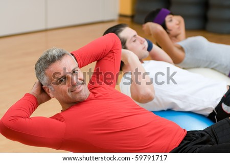 Healthy people with mature instructor doing sit-ups at gym - stock photo