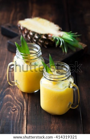 Healthy pineapple smoothie in mason jars, selective focus - stock photo