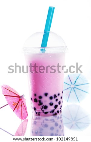 Healthy pink berry bubble tea with a good head of froth or bubbles from shaking and colourful purple boba - stock photo