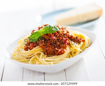 Healthy plate of Italian spaghetti topped with a tasty tomato and ground beef Bolognese sauce and fresh basil on a rustic white wooden table - stock photo