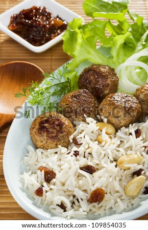 Healthy plate of spicy Indian lamb meatballs, or koftas, with Basmati rice with nuts and fruit, and salad. - stock photo