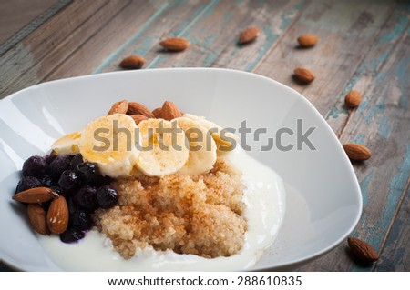 Healthy porridge of quinoa and kefir yogurt served with banana, blueberries, almonds and a sprinkling of chia seeds.Served on a rustic blue wooden table. - stock photo