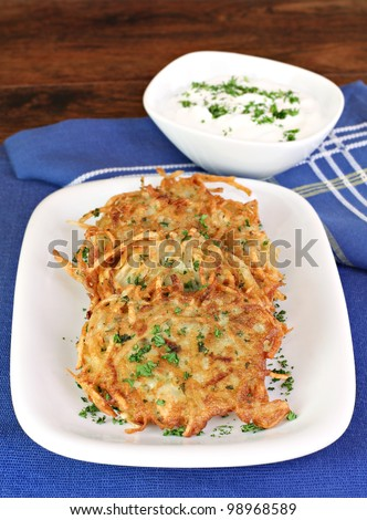 Healthy potato pancakes or latkes served with sour cream and garnished with fresh parsley. - stock photo