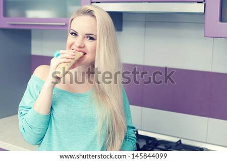 Healthy pregnancy concept. Portrait of a lovely and funny young pregnant woman eating her brioche (bread)  in her modern hi-tech kitchen. Trendy clothing on girl. Copy-space. Indoor shot - stock photo