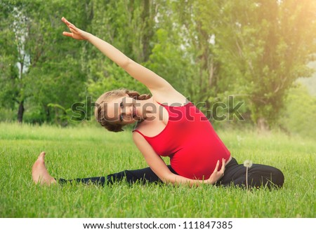 healthy pregnant woman doing yoga in nature outdoors - stock photo